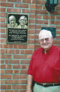 Dr. Coulter poses with the plaque honoring him and his mother mounted on the library building.
